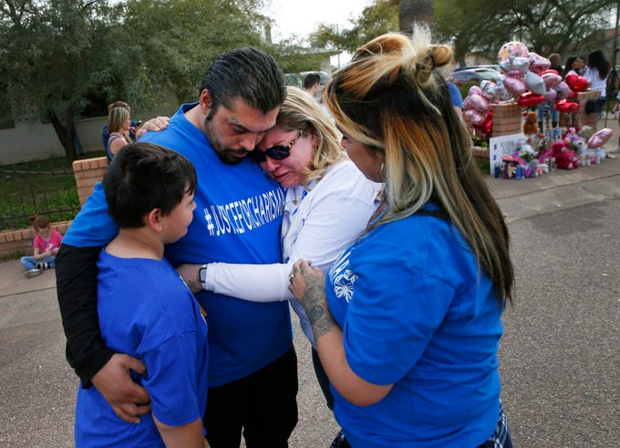 Priscilla Marquez (center) is consoled by her brother Christopher Washman, his son Xavier (left) and his wife Vanessa (right) during a vigil outside the home where three of her children were placed in foster care in Phoenix Feb. 9, 2020.  Marquez says she is the biological mother of Chariama Marquez, whose remains were discovered in the attic after a fire last month.