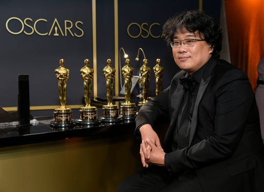 El escritor director Bong Joon-ho posa con las estatuillas conquistadas por 'Parasite'.