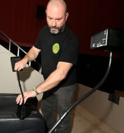 RC Theatres manager Chris Young installs a closed caption device in the cupholder of a seat at the theater in York Township Monday, Feb. 10, 2020. The theater is upgrading with ADA-compliant equipment, includingdescriptive audio, closed captioningand assisted listening. Bill Kalina photo