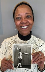 Donna Stephens holds a photograph of herself during the time she was the first African American majorette at York High.