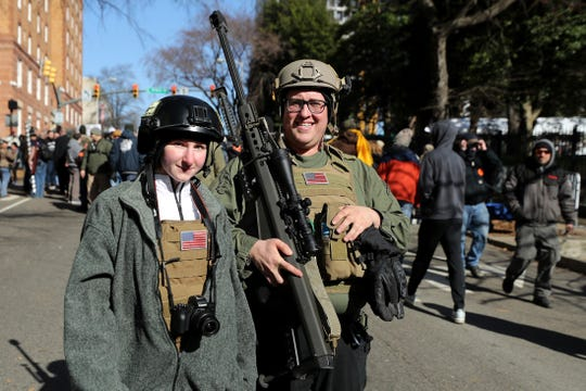 Brandon Lewis (R) of Brockport, New York, carries a .50-caliber Barrett M82A1 rifle through the streets following a rally organized by The Virginia Citizens Defense League on Capitol Square near the state capitol building January 20, 2020 in Richmond, Virginia.
