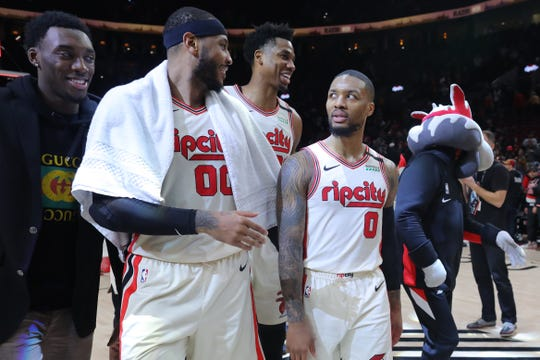 Portland Trail Blazers forward Carmelo Anthony (00), center Hassan Whiteside (21) and guard Damian Lillard (0) celebrate a 115-109 win over Miami Heat at Moda Center.