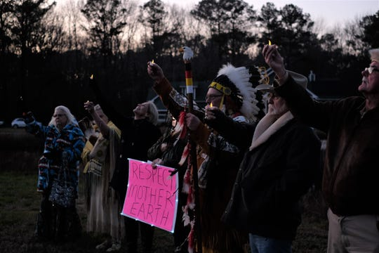 Chief Michael Quiet Bear Morabito, along with other Assateague and Chincoteague Native Americans, hold up candles during a vigil over a proposed development that could wipe out part of Sussex history.