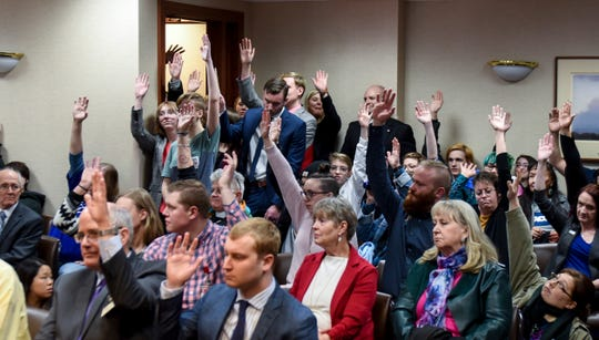 People opposing House Bill 1057 raise their hands after the South Dakota Senate committee hearing on Monday, Feb. 10, 2020 at the state capitol in Pierre, S.D.