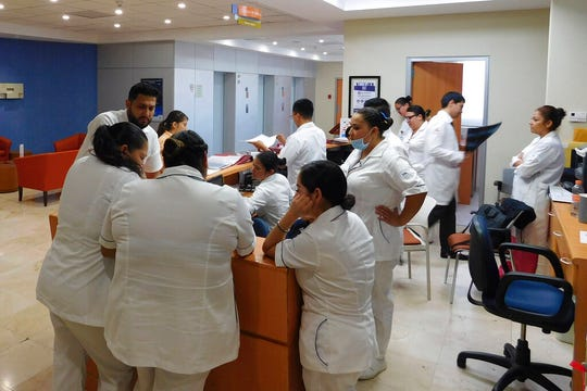 Doctors and nurses gather at a reception desk at Hospital Angeles in Tijuana, Mexico.