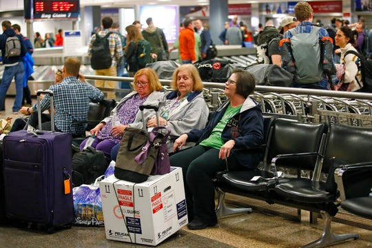 In this Jan. 31, 2020, photo, Ann Lovell, right, sits with her box of prescriptions after returning to Salt Lake City International Airport following her visit to Tijuana, Mexico.
