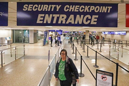 In this Jan. 31, 2020, photo, Ann Lovell stands at the security checkpoint before her flight from Salt Lake City International Airport to San Diego.