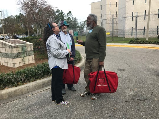 Susan Caplowe, Darwin Gamble, and Barry Munroe, prepare to enter the Leon County Detention Facility to register voters for the March presidential primary