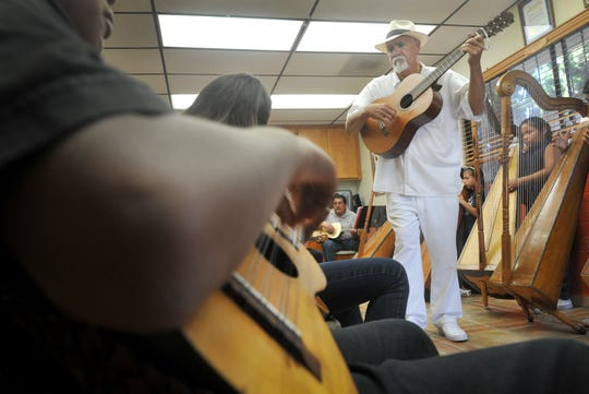 "Xavier Montes watches students play guitar while working with the Inlakech Cultural Arts Center's ""Angels with Harps"" program in 2015."
