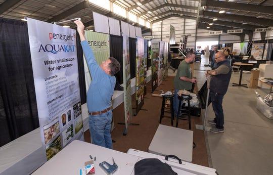 Derek Pratt, left, Justin Henson and Greg Verhoeven assemble the Penergetic booth in Pavilion C during the World Ag Expo on Monday, February 10, 2020.
