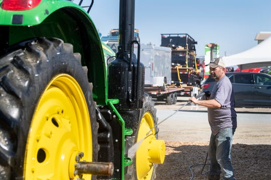 Charlie Dondlinger sprays off John Deere tractors in preparation for the World Ag Expo on Monday, February 10, 2020.
