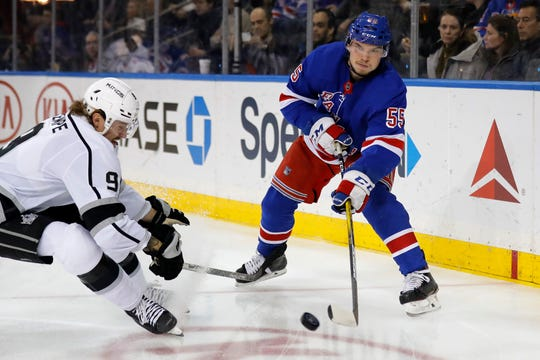 New York Rangers defenseman Ryan Lindgren (55) clears the puck past Los Angeles Kings center Adrian Kempe (9) in the first period of an NHL hockey game Sunday, Feb. 9, 2020, in New York. (AP Photo/Adam Hunger)