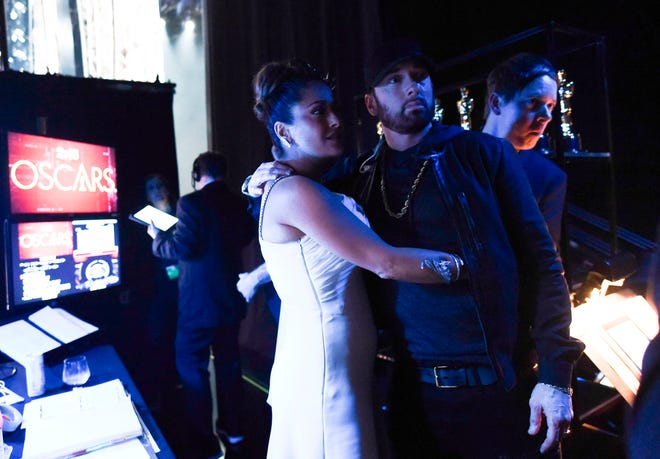 Salma Hayek Pinault gives a hug to Eminem backstage during the 92nd Annual Academy Awards.