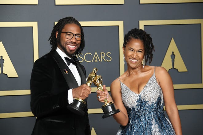 """Matthew A. Cherry and Karen Rupert Toliver celebrate backstage with their trophies after receiving the Oscar for best animated short film for """"Hair Love."""""""