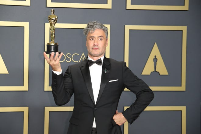 """""""Jojo Rabbit"""" director, writer and star Taika Waititi shows off his Oscar statuette for best adapted screenplay in his very individual way."""