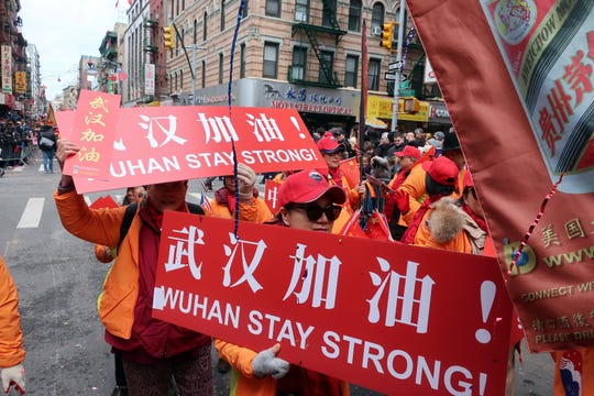 People carry signs in support of Wuhan, China, at the center of the coronavirus outbreak, during the Lunar New Year parade on Feb. 9, 2020, in Manhattan's Chinatown.