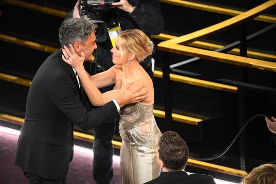 """Jojo Rabbit"" star Scarlett Johansson congratulates Taika Waititi as he accepts the Oscar for best adapted screenplay."