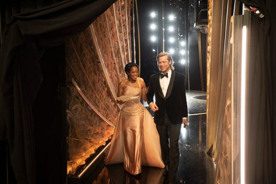 Brad Pitt walks off the stage with presenter Regina King after he won the Oscar for best supporting actor at the Oscars.