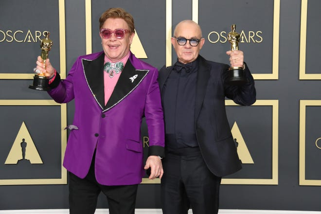 """Longtime musical partners Elton John, left, and Bernie Taupin celebrate backstage after winning the Oscar for best original song for """"(I'm Gonna) Love Me Again"""" from """"Rocketman."""""""