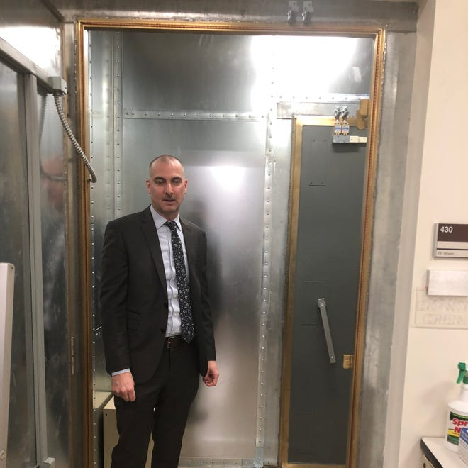 Steven Moran, director of the High Technology Analysis Unit at the Manhattan District Attorney's Office, stands outside the vault where computers bombard seized smartphones with codes in order to guess the passcodes and enable investigators to access their data. New batches of phones are moved into the chamber like unbaked cookies and others are moved out before they're done.