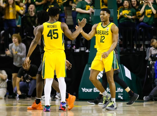 Baylor guard Jared Butler slaps the hand of guard Davion Mitchell (45) after during the team's defeat of Oklahoma State at Ferrell Center.