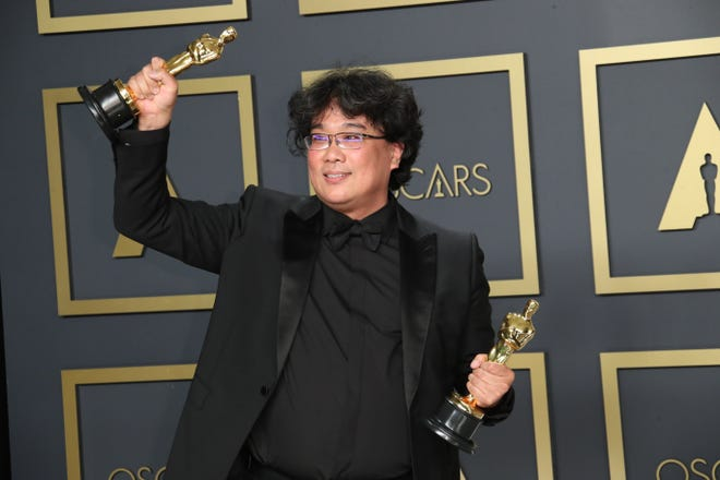 """Director Bong Joon-Ho offers a two-fisted Oscar salute after his film, """"Parasite,"""" won best picture and other honors at Sunday's Academy Awards ceremony."""