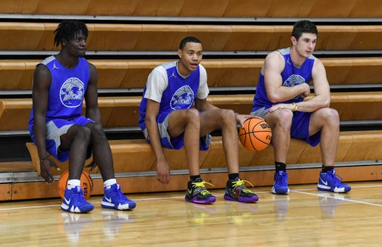 Bryce McGowens of Wren High School sits with teammates Wren senior Dez Frazier(4), left, and Wren senior Eli Wilson(12), right, watching teammates run a five-on-five in practice at the school gymnasium in Piedmont Monday.