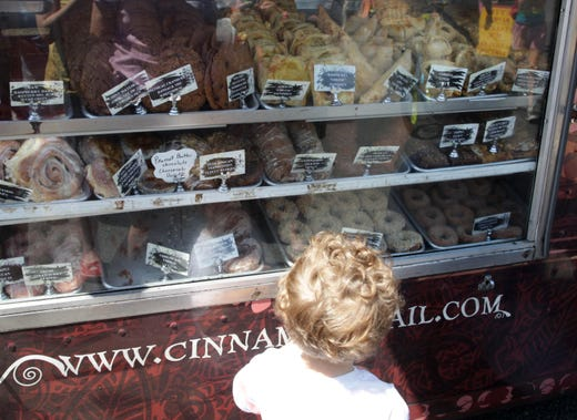 A child looks over pastries at the Cinnamon Snail, vegan, organic, food truck, at the farmers market in Red Bank in 2012.