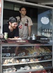 Adam Sobel, owner and Anthony Cappadona,  talk with customers while working on the  Cinnamon Snail, vegan, organic, food truck, at the farmers market in Red Bank in 2012.