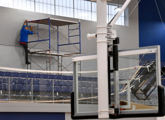 Meguel Suell climbs scaffolding Tuesday at the Dodge Jones Youth Sports Center.