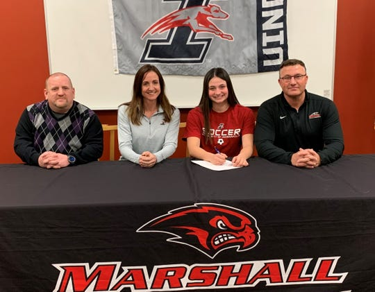 Marshall's Danielle DeVine signs to play women's soccer at the next level at the University of Indianapolis. She is joined by her coach Hans Morgan, at left, and her parents Janet DeVine and Jason DeVine.