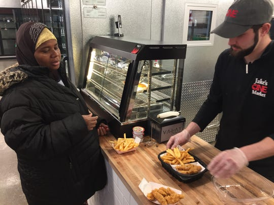 Fatuma Abdul of Burlington orders chicken tenders and French fries from Joe Rivers of Colchester at Jake's ONE Market in Burlington on Feb. 10, 2020.