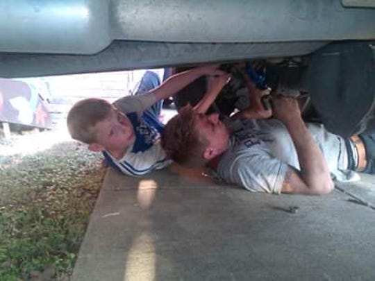 Sam Reynolds, left, and Harley Livingston work underneath a car in this undated photo. Sam was shot to death Thursday, Feb. 6, 2020 in Arlington, Texas. Livingston was one of several male role models who are credited with teaching Sam his values growing up.