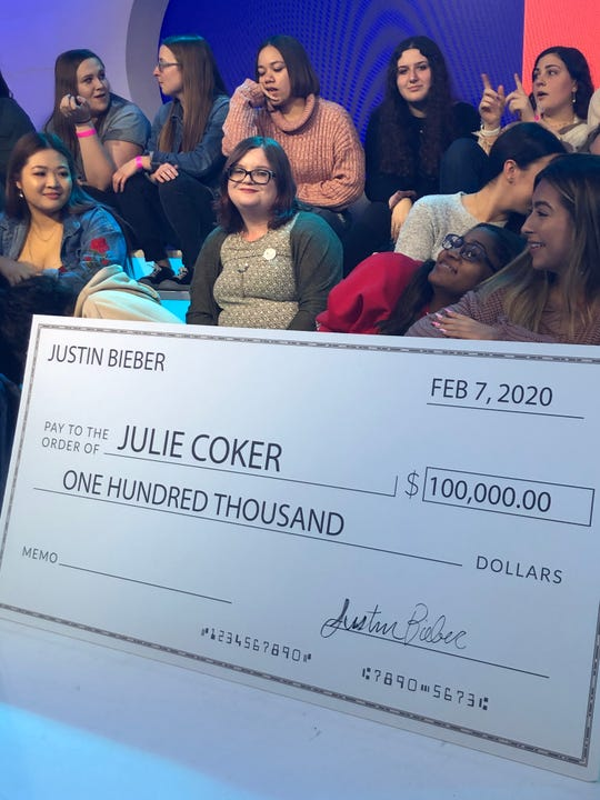 Stockton University student Julie Coker (center) is shown with the check that singer Justin Bieber presented to her on Feb. 7 for her work in the mental health area.