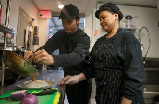 Mark Reyta and his mother Everlinda Reyta, chefs/owners of Reyta's Filipino Cuisine, prepare a Pork Sisig dish in the kitchen of Reyta's Filipino Cuisine in Cherry Hill.