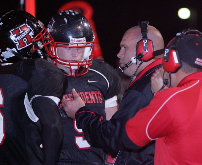 Harding High School head football coach Heath Hinton, second from right, talks with players during a home game against Findlay.