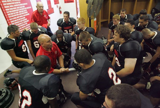Harding head coach Heath Hinton shares a quite moment before the President's home opener against Marysville on Friday, Aug. 27, 2010.