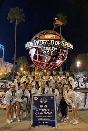 Milford High School's competitive cheer team shows off it championship banner after winning a title at the UCA National Cheer Championship Feb. 9.