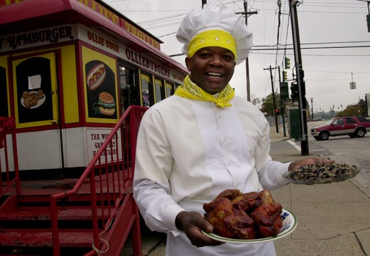 Marvin (Ollie) Smith stands in front of Ollie's Trolley on Liberty holding some BBQ chicken and black beans and rice on October 26, 2002.