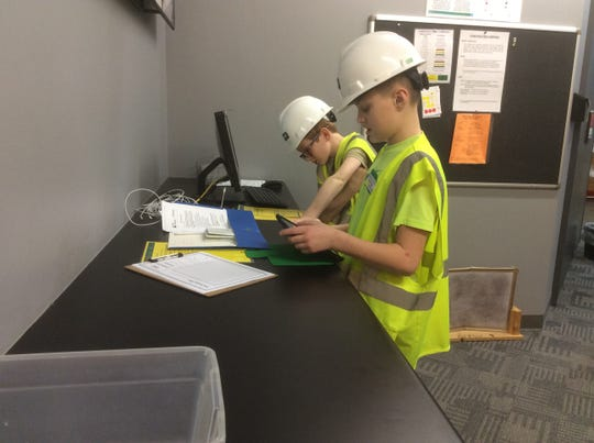 """Woodside Middle School, Saydel, students recently participated in Junior Achievement BizTown. They were able to live the experience of personal finance in a real-life setting of stores, shops, and financial institutions by basically becoming """"an adult for the day."""" Pictured here are Woodside sixth grader Blake Brown acting as a construction company CEO, Keagan Frideres acting as a CFO. They are working hard to make their company a success."""