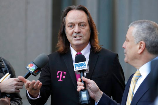 T-Mobile chief executive John Legere speaks to reporters as he leaves the courthouse in New York, Wednesday, Jan. 15, 2020. Legere was in court to hear closing arguments in the case that could permit T-Mobile to merge with Sprint.