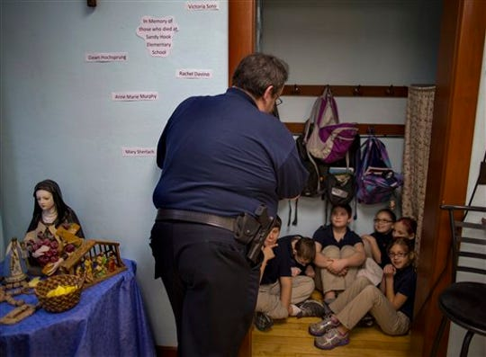 In this file photo of Jan. 14, 2013, New Washington, Ohio, Chief of Police Scott Robertson talks with fourth grade students as they huddle in closet a during a lockdown drill at the St. Bernard School in New Washington, Ohio, a month after the Sandy Hook Elementary School massacre in Newtown, Conn., that killed 26 people in December. Inspired by the memories of those who lost their lives, St. Bernard School's principal decided to hold lockdown drills on the 14th of each month to refine a safety plan and increase school security.