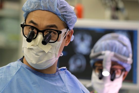 In this Jan. 14, 2020 photo, neurosurgeon Dr. Andrew Ko, left, of the University of Washington School of Medicine, wears glasses with magnifying lenses in the operating room as he works with senior resident Dr. Ariana Barkley, right, to perform brain surgery on Genette Hofmann at Harborview Medical Center in Seattle in hopes of reducing the epileptic seizures that had disrupted Hofmann's life for decades.
