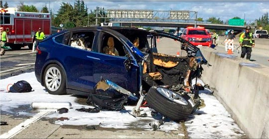 In this March 23, 2018, file photo provided by KTVU, emergency personnel work a the scene where a Tesla electric SUV crashed into a barrier on U.S. Highway 101 in Mountain View, Calif. The Apple engineer who died when his Tesla Model X crashed into the concrete barrier complained before his death that the SUV's Autopilot system would malfunction in the area where the crash happened. The complaints were detailed in a trove of documents released Tuesday, Feb. 11, 2020, by the U.S. National Transportation Safety Board, which is investigating the March, 2018 crash that killed engineer Walter Huang.