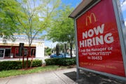 A help wanted sign appears on a bus stop in front of a McDonald's restaurant in Miami.