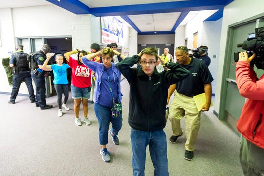 In this Friday June 9, 2017 file photo, students are led out of school as members of the Fountain Police Department take part in an Active Shooter Response Training exercise at Fountain Middle School in Fountain, Colo.