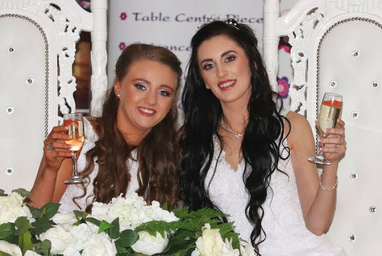 Robyn Peoples, left, 26, and Sharni Edwards, 27, pose together after becoming the first same sex couple to marry in Northern Ireland, in Carrickfergus, Northern Ireland, Tuesday Feb. 11, 2020. Two women tied the knot Tuesday in Northern Ireland's first same-sex wedding, after the region became the last part of the United Kingdom to legalize gay marriage.