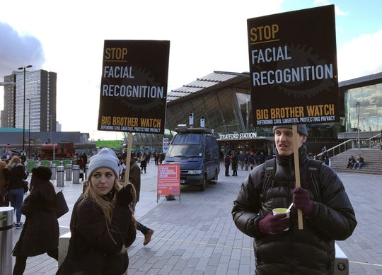 """Rights campaigner Silkie Carlo, left, demonstrates in front of a mobile police facial recognition facility outside a shopping centre in London Tuesday. """"We don't accept this. This isn't what you do in a democracy,"""" said Carlo, director of privacy campaign group Big Brother Watch."""