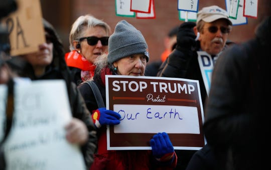 A protester holds a placard at a rally of advocates to voice opposition to efforts by the Trump administration to weaken the National Environmental Policy Act, which is the country's basic charter for protection of the outdoors on Tuesday, Feb. 11, 2020, in Denver.