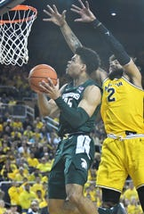 Michigan forward Isaiah Livers defends a shot by Michigan State forward Malik Hall in the first half of Saturday's game.